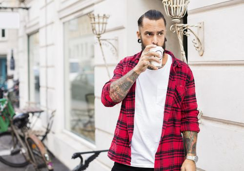 Pierced and tattooed man drinking coffee outside