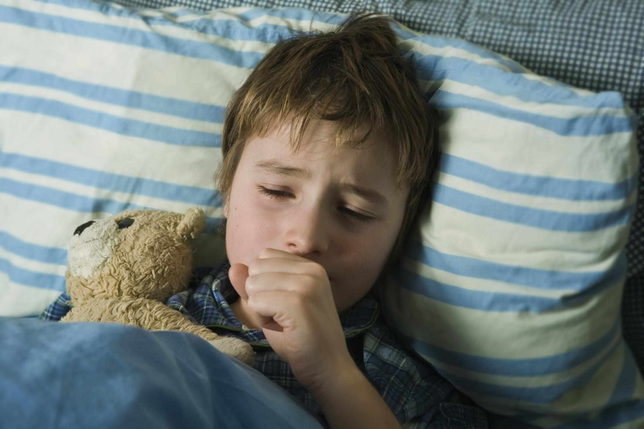 Young child in bed with teddy bear
