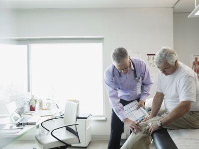 Doctor examining senior mans knee in examination room
