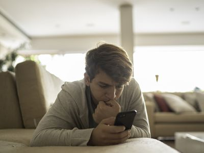 Teenager boy biting nails while using smartphone
