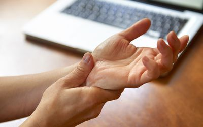 Photo of a person holding a sore wrist