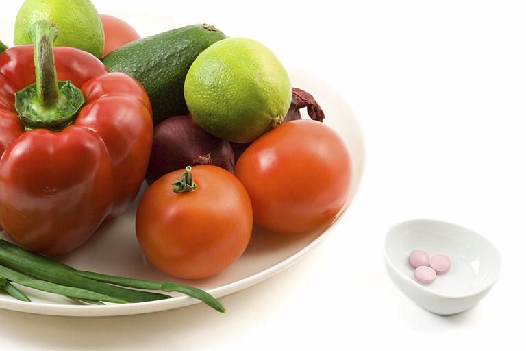 Plate of vegetables and fruit (red bell pepper, tomatoes, avocado, onions, and limes) and a bowl of three pink pills