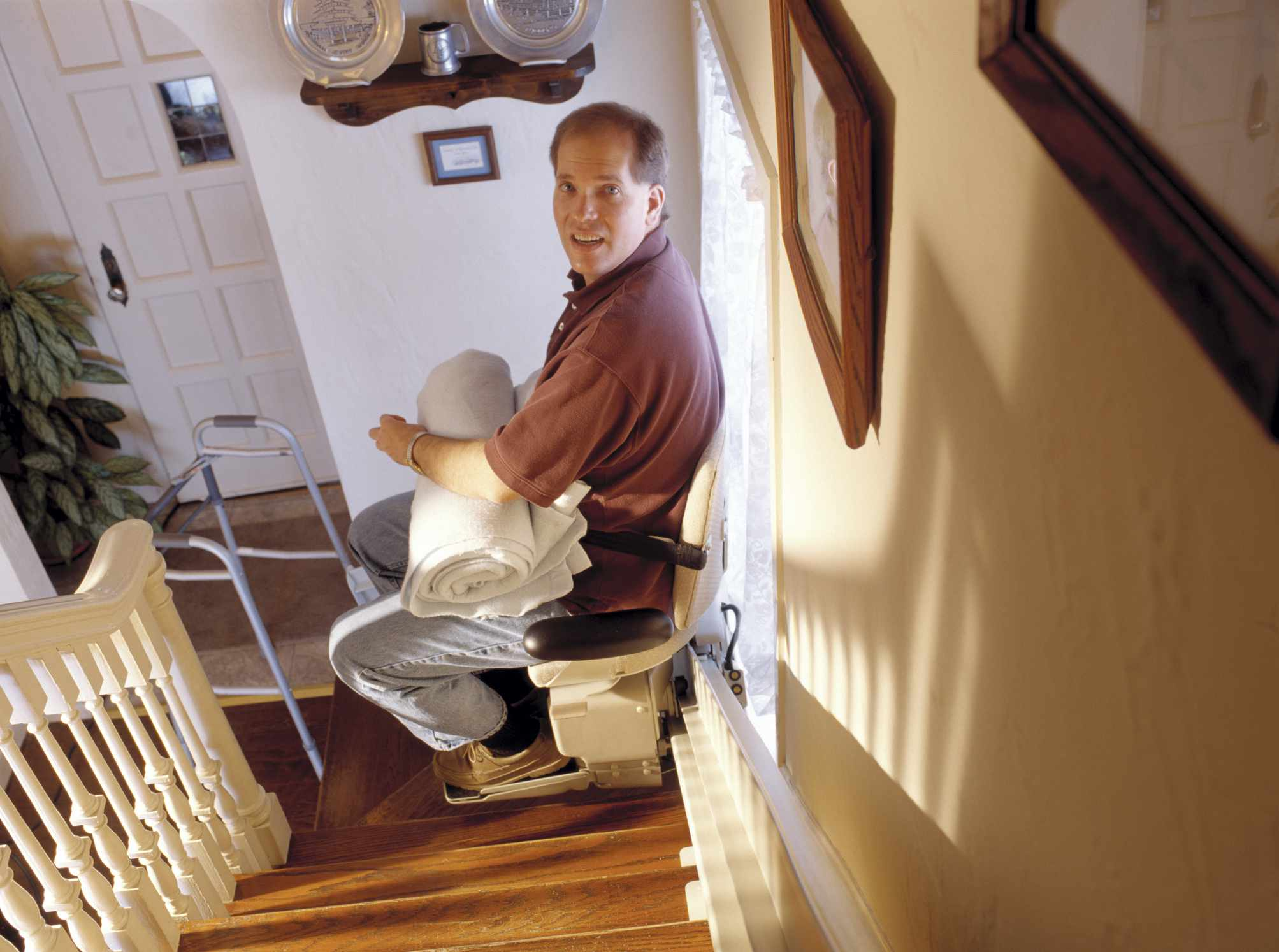 Man moving up a stair lift in his home
