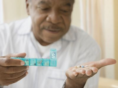 African man holding daily pill box with pills
