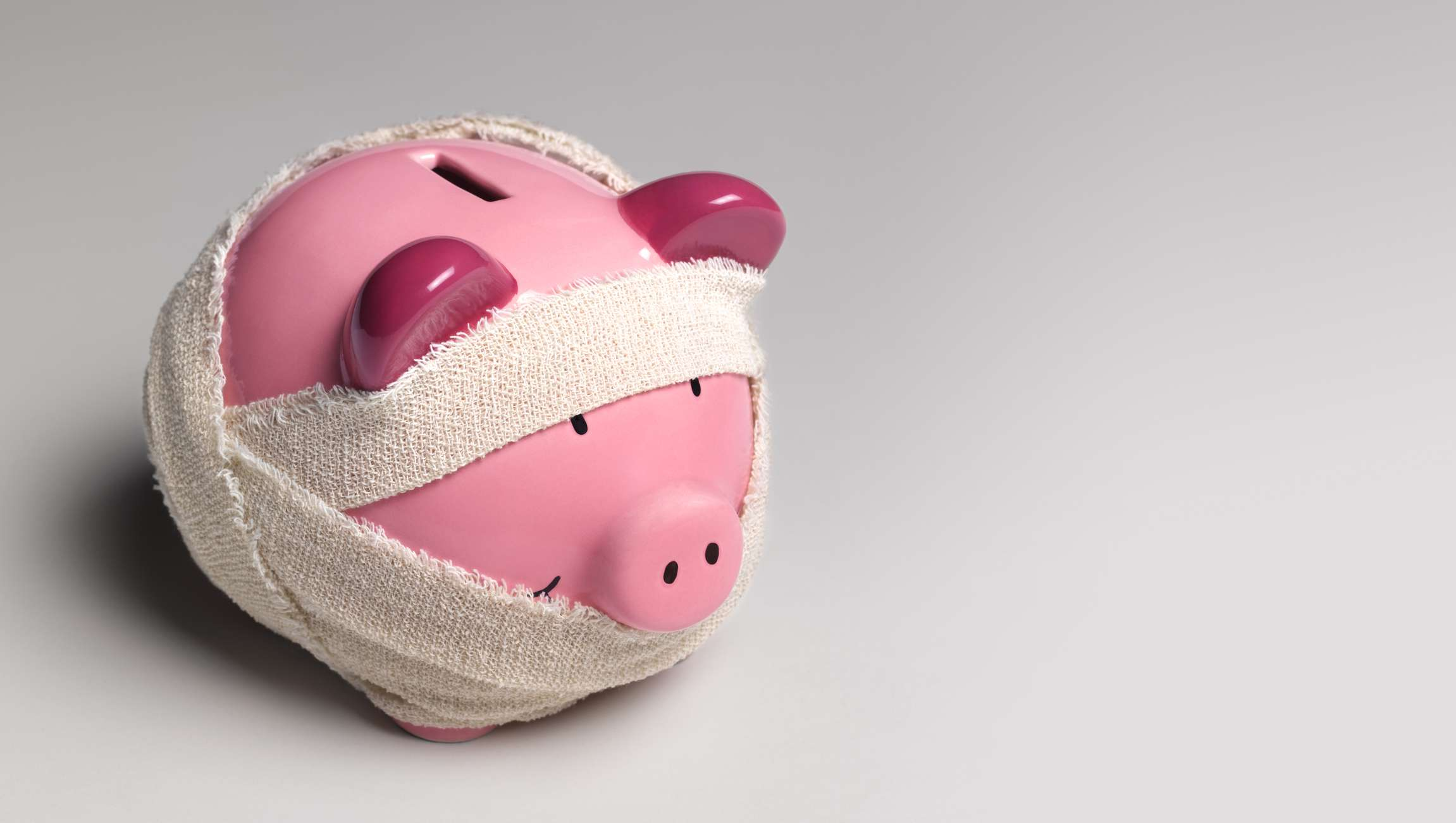 Piggy bank wrapped in bandages on a gray background