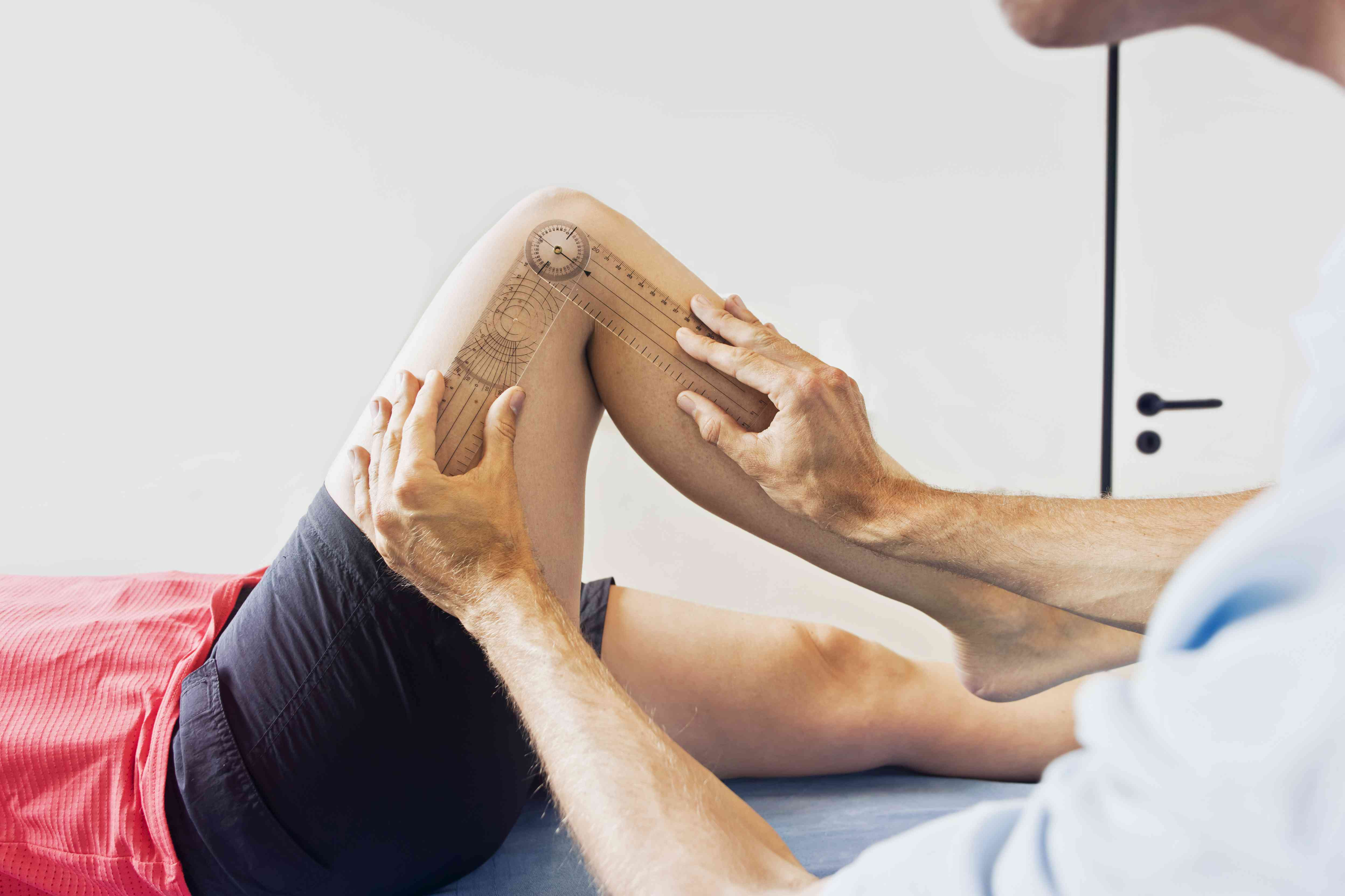 Doctor measuring person's knee range of motion