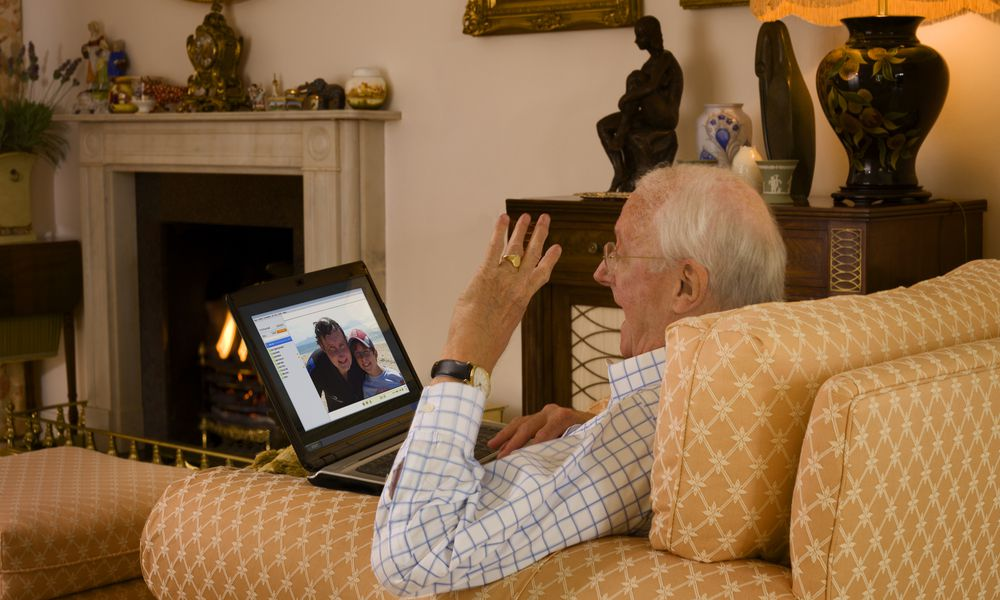 Old man video chatting with son and grandson.