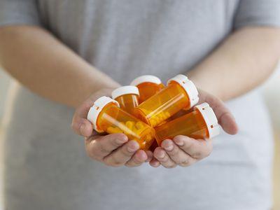 Woman holding prescription pill bottles