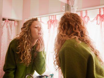Teen girl inspecting her skin in the mirror