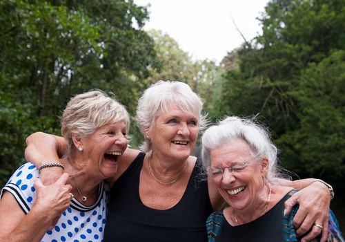 Photo of a group of senior women standing outside and laughing