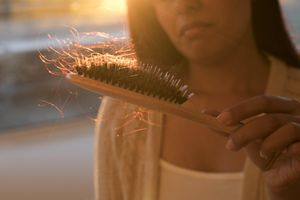 Clumps of hair on a hairbrush being held by a woman whose face is not in full view.