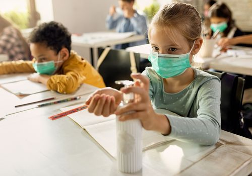 Two children at school wearing masks and using hand sanitizer.