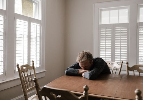A white man seated at a kitchen table with his head resting on his arms; he appears down or depressed.