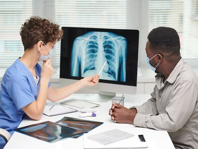 Side view shot of professional pulmonologist demonstrating x-ray shot to patient on computer screen and explaining something to him - stock photo