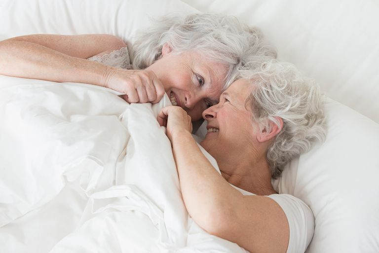 Older Caucasian lesbian couple laying in bed
