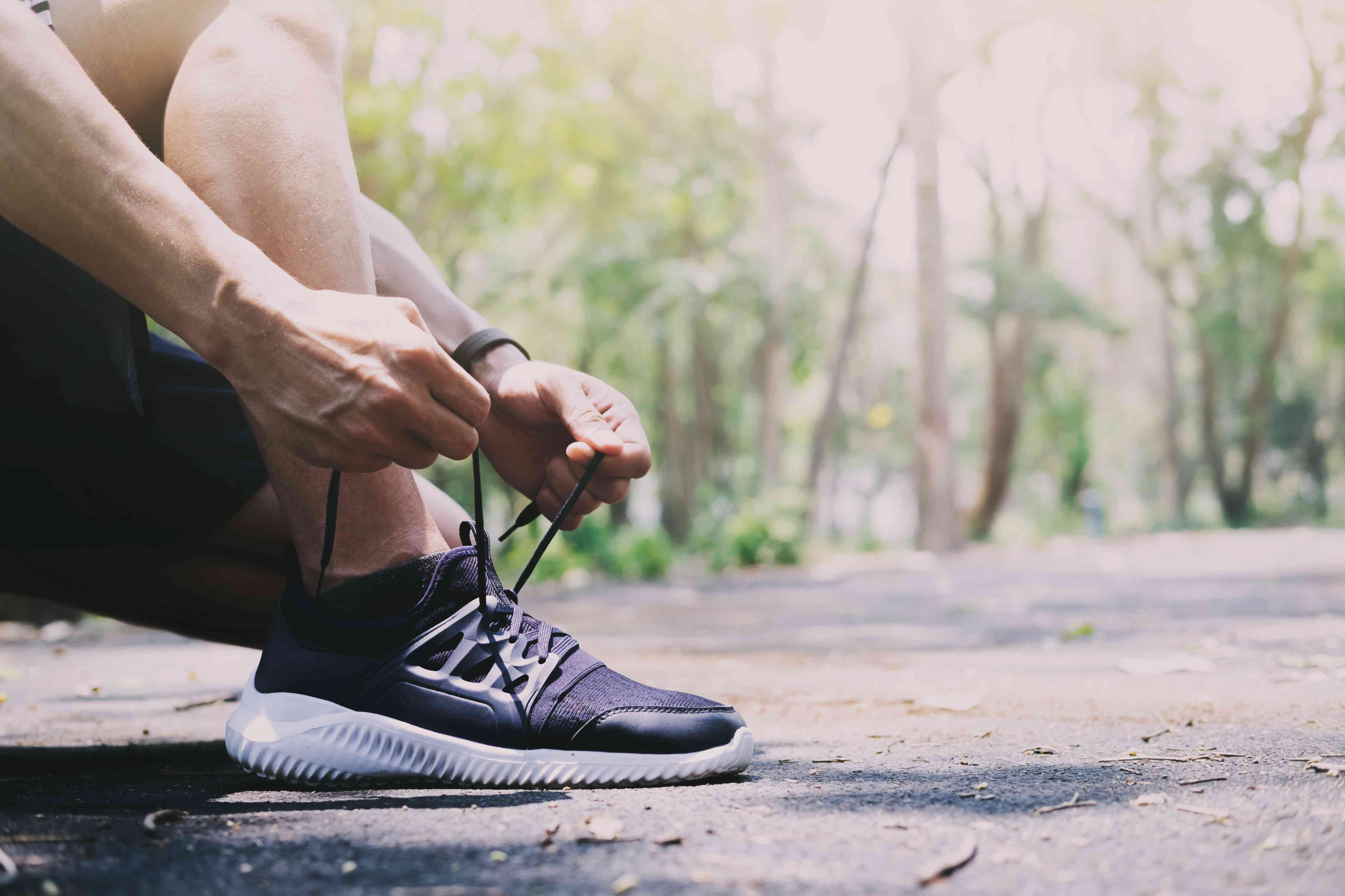 Person lacing up a sneaker in an outdoor environment