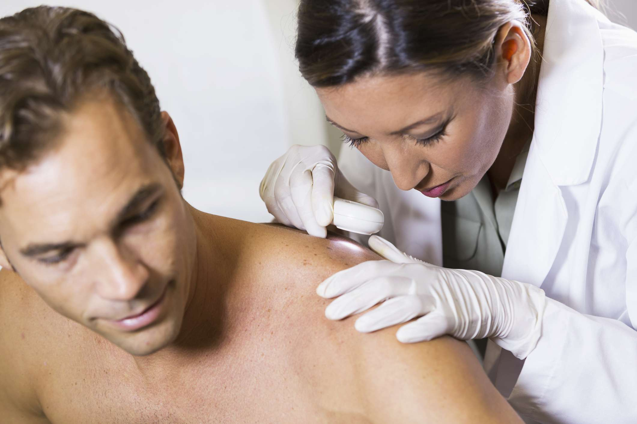 Female doctor examining male patient with dermascope, looking for signs of skin cancer