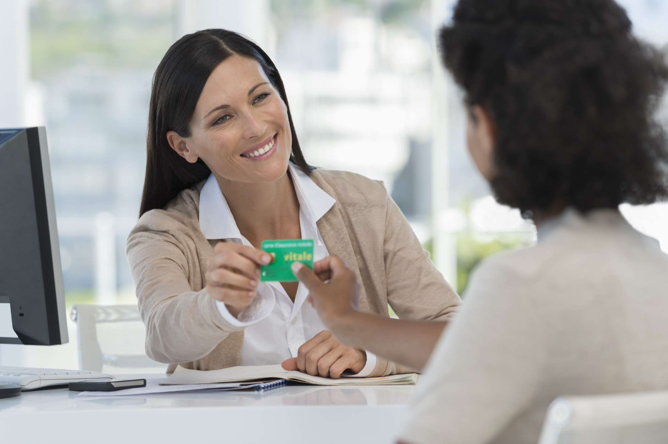 Receptionist giving insurance card to patient
