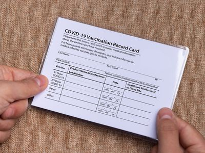 Close up of a white person's hands holding a laminated COVID vaccine card.