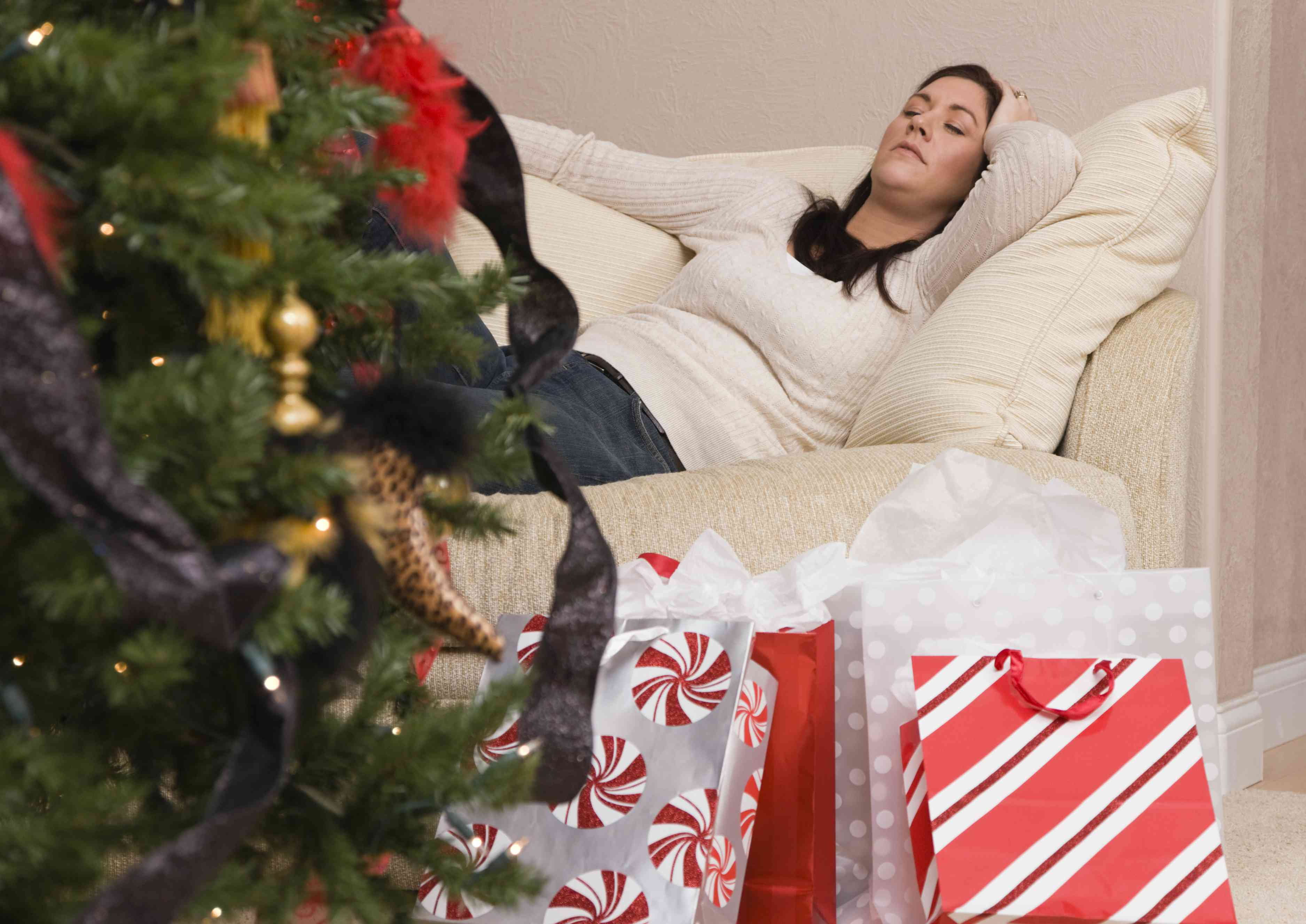 A woman napping near her Christmas tree