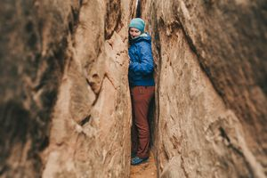 A woman squeezes between two rock canyon walls