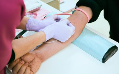 Female nurse is taking blood of a senior patient at hospital