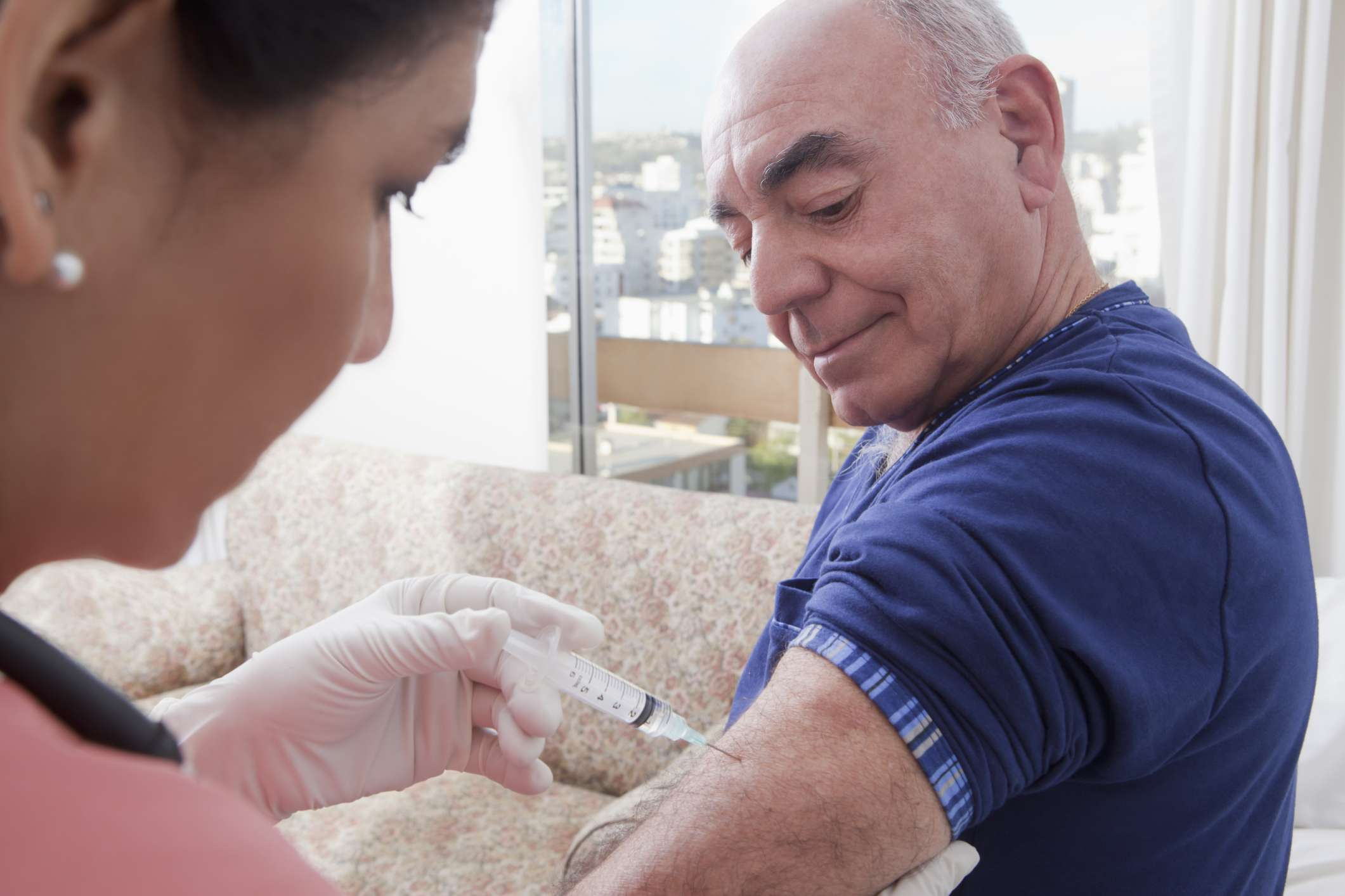 A woman is giving a man an injection in the arm. The woman is on the left of the photo, the man is to the right and wearing a short sleeve blue shirt.