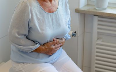 Midsection Of Senior Woman Suffering From Stomachache