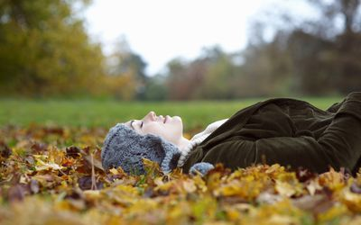 Woman resting on leaves with her eyes closed