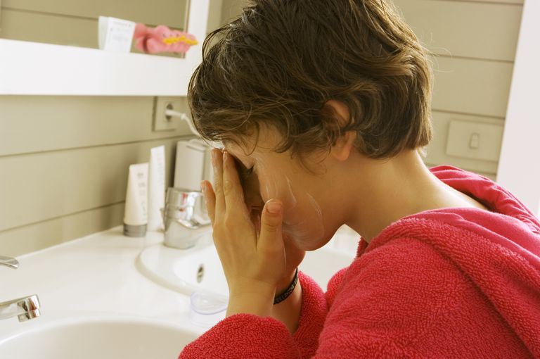 A preteen washing his face in the bathroom