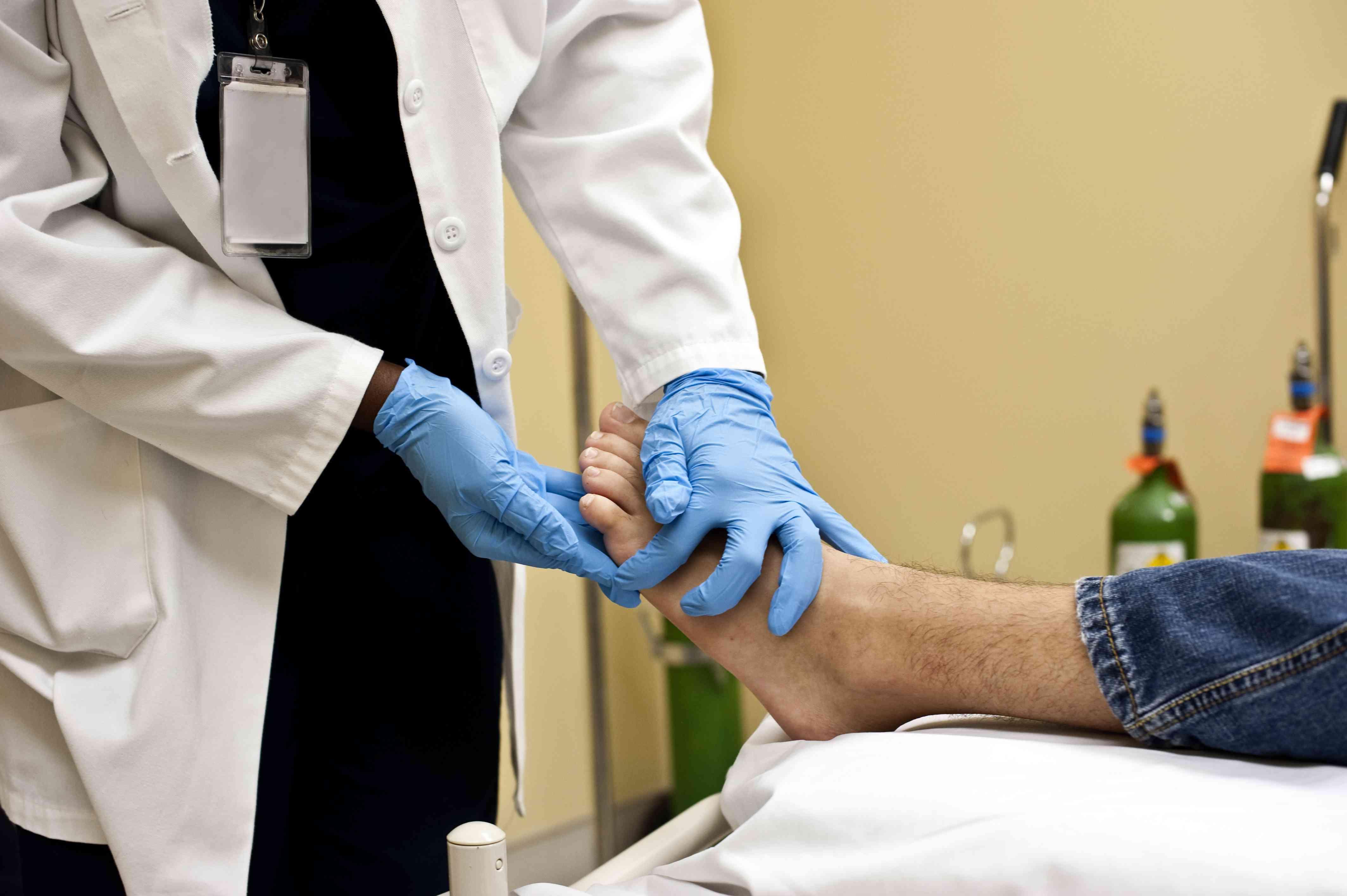 A podiatrist examining his patient's foot