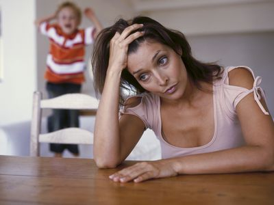 A stressed mom while her child screams behind her.