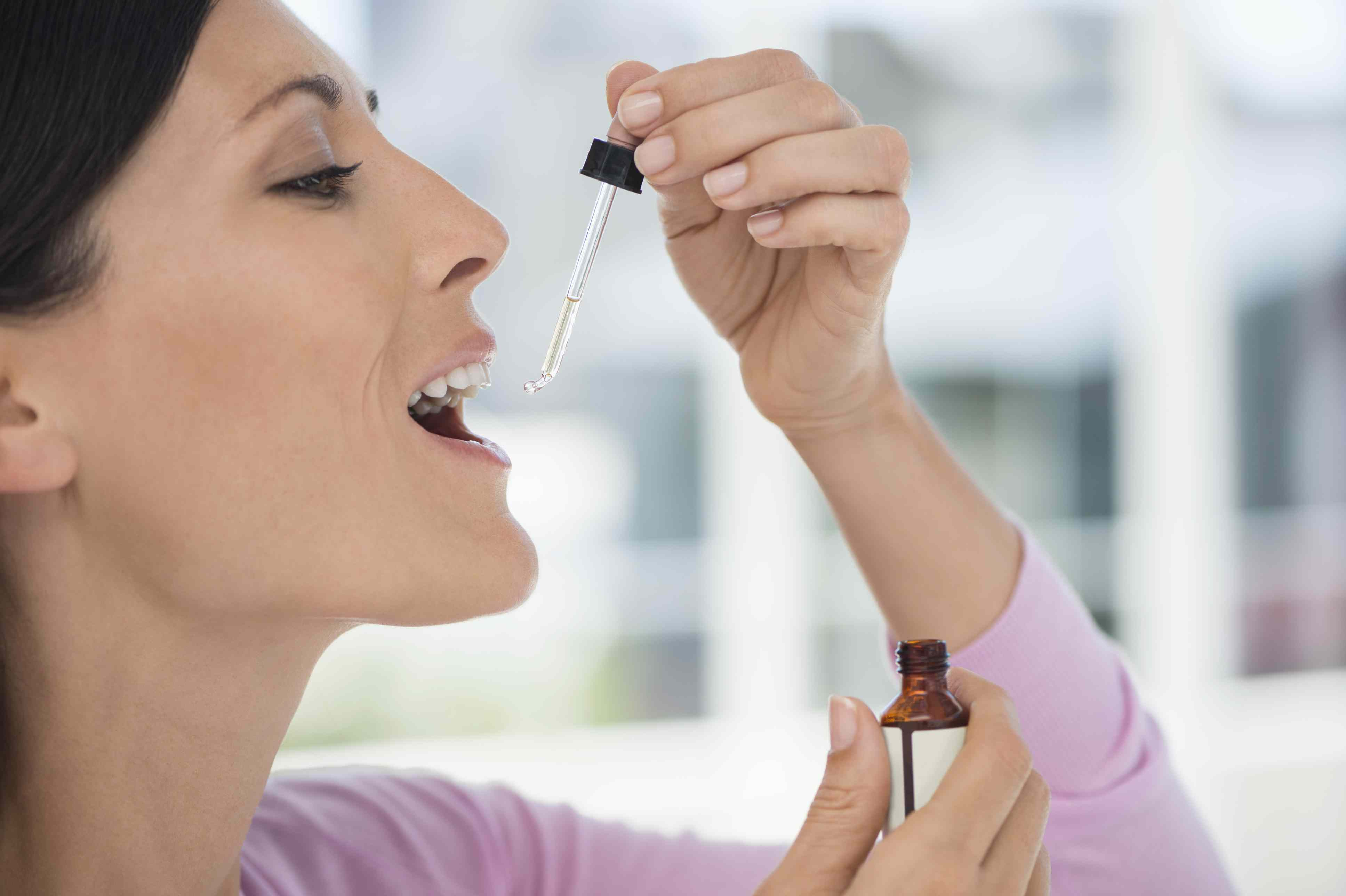 A woman taking homeopathic medicine