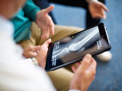 Shot of a doctor explaining x-ray test result to patient in clinic. Focus on digital tablet screen with medical scan image.