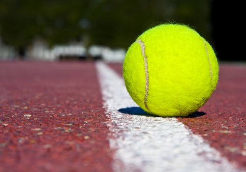tennis ball placed on a white line outside