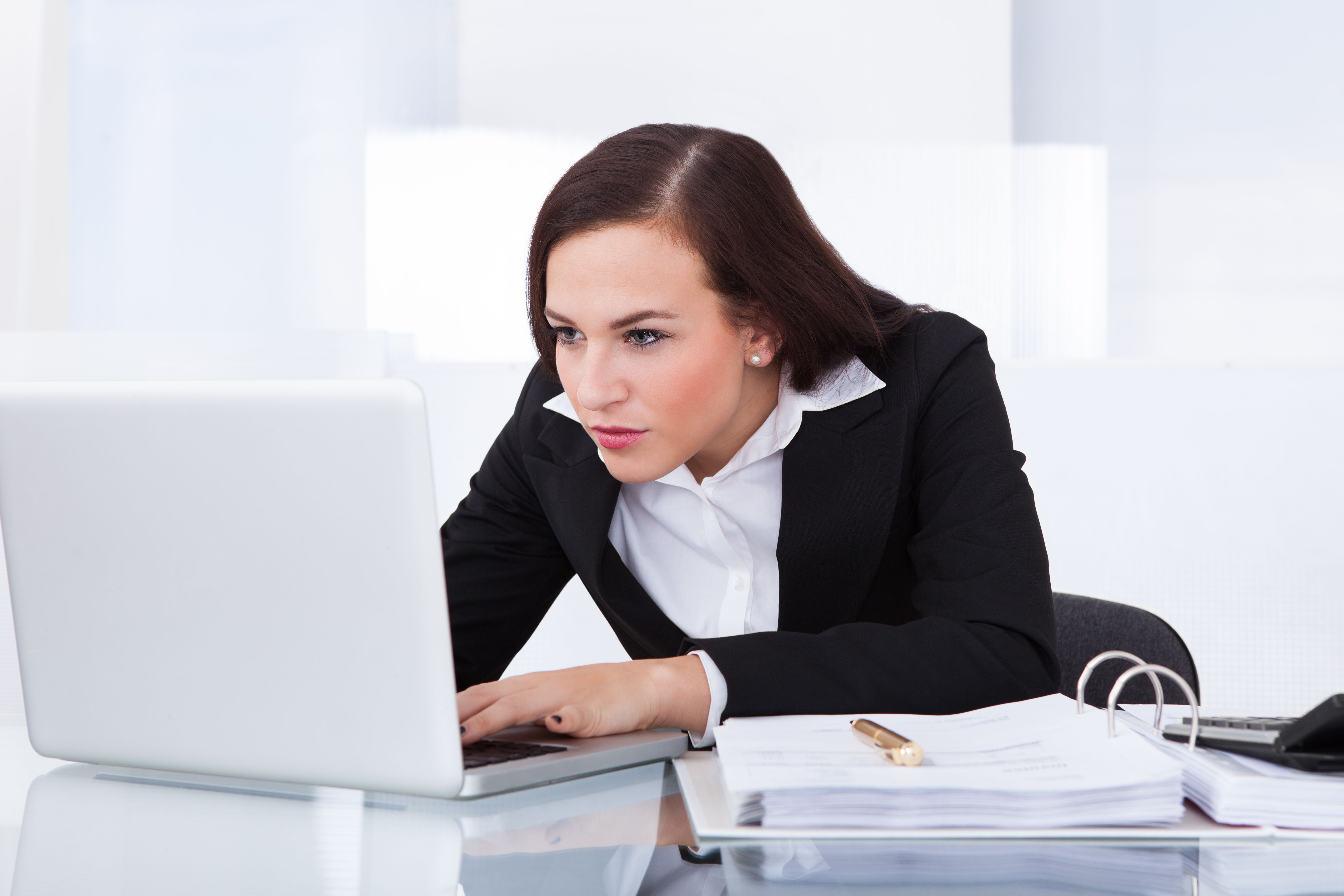 Woman craning her neck to see her laptop screen.