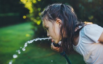 young girl drinking from garden hose