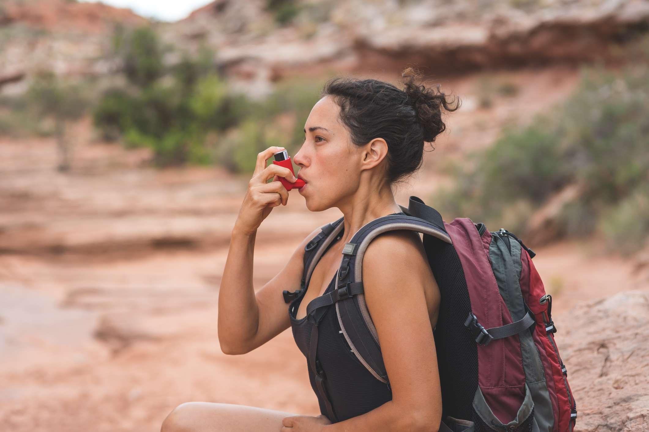 A hiker with asthma using her inhaler