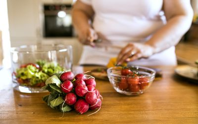 Unrecognizable overweight woman at home preparing a healthy vegetable salad in her kitchen.