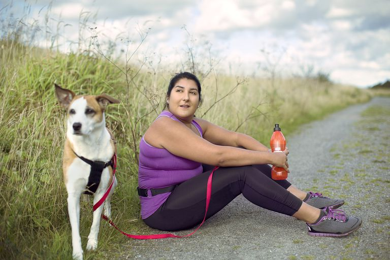 Female runner sitting on country road with dog