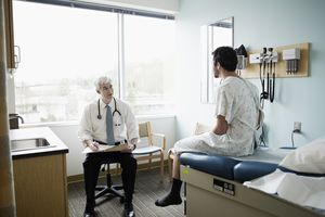 Male patient in gown sitting on exam table in discussion with doctor in exam room
