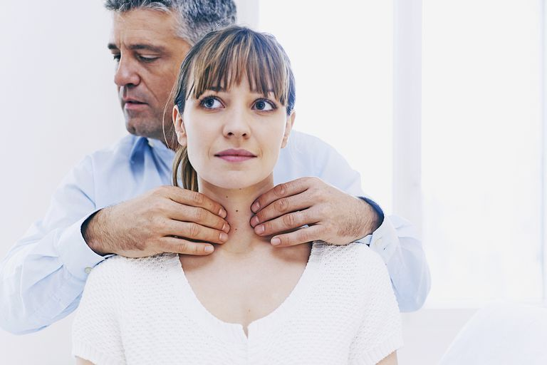 A doctor feels a woman's neck to check her thyroid gland.