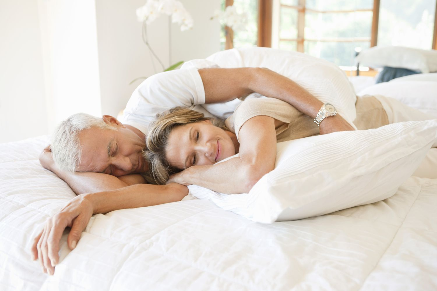 Happy mature couple lying together on a bed