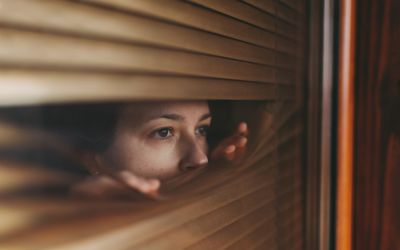 Woman at home during COVID-19 pandemic is looking through window
