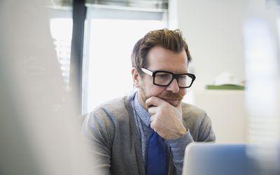 Man wearing glasses on laptop
