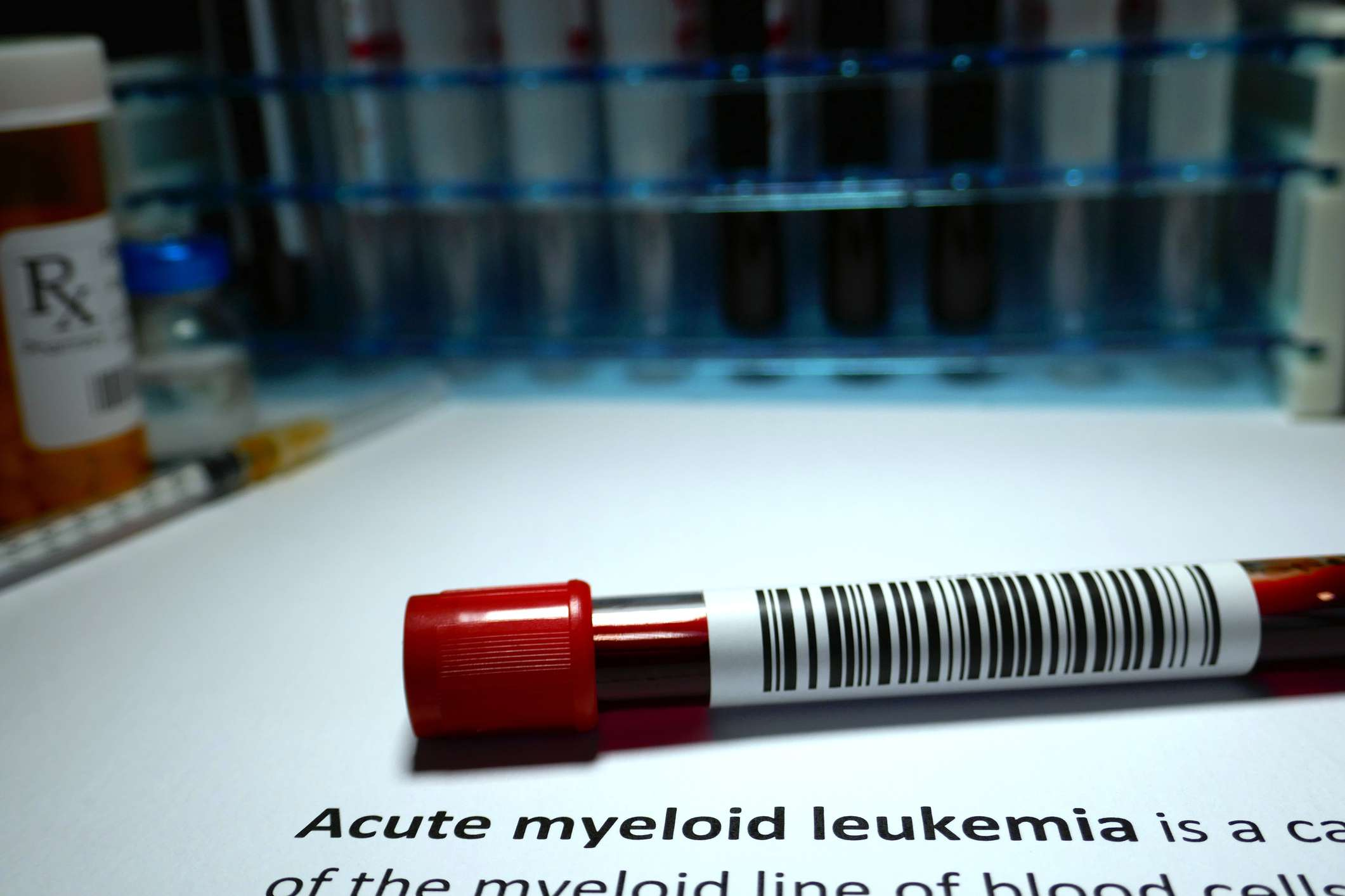 Vial of blood with the definition of acute myeloid leukemia beneath this.