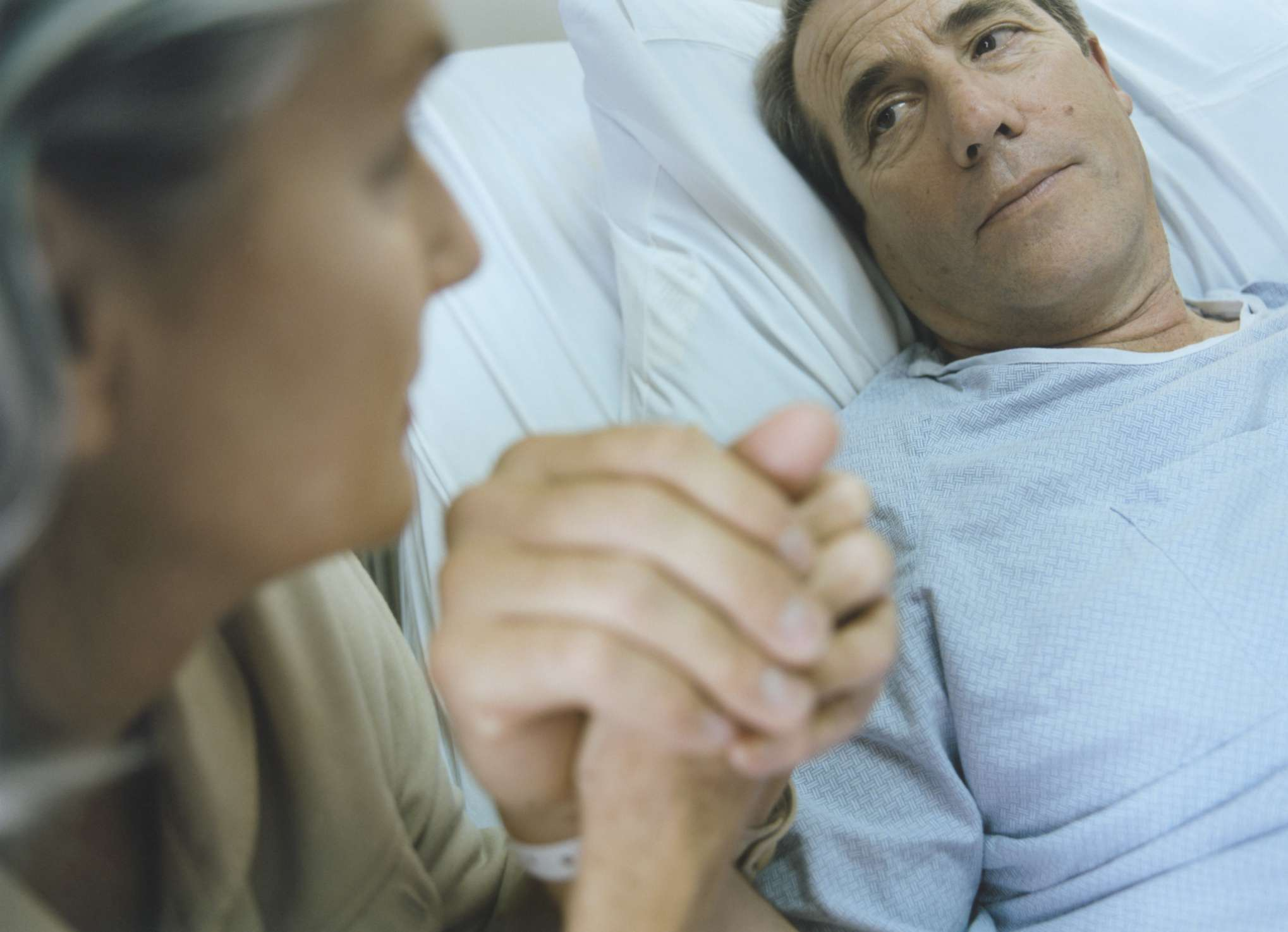man in hospital bed holding wife's hand