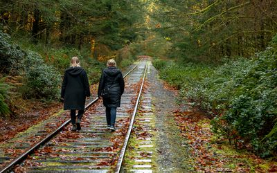 Rear view of a parent and teen walking along a railway track in autumn, Goldstream, Vancouver Island, Canada