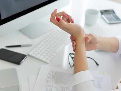 Woman working at a white desk grasping her left wrist