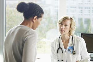 Female doctor and patient talking in exam room